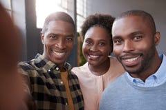 Colegas africanos jovenes del trabajo que sonríen junto en una oficina Foto de archivo libre de regalías