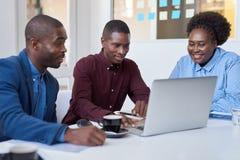 Colegas africanos jovenes que trabajan en un ordenador portátil en una oficina Imagen de archivo libre de regalías
