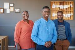 Colegas africanos sonrientes del negocio que se unen en una oficina moderna Fotos de archivo libres de regalías