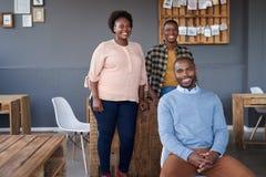 Colegas africanos sonrientes que trabajan junto en una oficina moderna Fotografía de archivo
