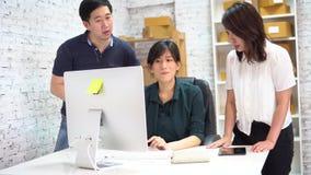Colegas asiáticos que discutem o projeto do negócio video estoque