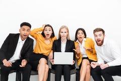 Colegas chocados que se sientan en oficina usando el ordenador portátil Imagenes de archivo