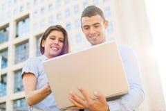 Colegas con el ordenador portátil en Front Of Company Imagen de archivo libre de regalías