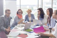 Colegas creativos del negocio que analizan las fotografías en la mesa de reuniones en oficina Foto de archivo