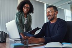 Colegas creativos sonrientes que trabajan junto en la oficina imágenes de archivo libres de regalías