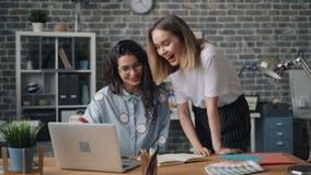 Colegas de las chicas jóvenes que hablan y que ríen mirando la pantalla del ordenador portátil en oficina almacen de video
