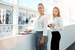 Colegas de las mujeres jovenes que se colocan en interior moderno de la oficina con la tableta digital y los documentos de papel Fotos de archivo libres de regalías