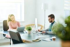 Colegas de oficina pensativos que usan los ordenadores imagen de archivo