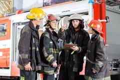 Colegas de Showing Something To del bombero en fotografía de archivo