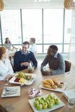 Colegas de sorriso do negócio que comem o café da manhã no bar do escritório Fotos de Stock