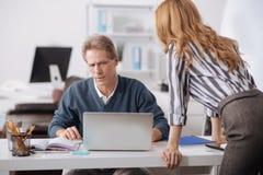 Colegas de trabalho confundidos que colaboram no centro de negócios Imagem de Stock Royalty Free