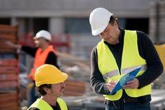 Colegas de trabalho da construção no trabalho foto de stock