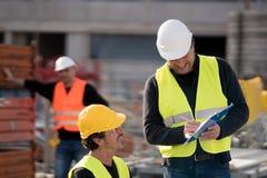 Colegas de trabalho da construção no trabalho fotografia de stock