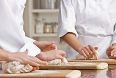 Colegas de trabalho do cozinheiro chefe que amassam a massa de pão na cozinha fotografia de stock
