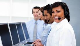 Colegas de trabalho felizes com auriculares sobre no centro de chamadas Imagem de Stock Royalty Free