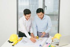 Colegas de trabalho masculinos que discutem ideias sobre o projeto no escritório, archit Imagens de Stock Royalty Free