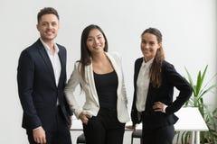 Colegas de trabalho milenares que levantam perto da mesa de escritório fotos de stock royalty free