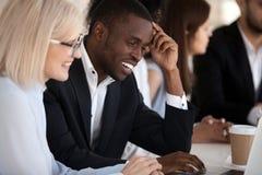 Colegas de trabalho multi-étnicos de sorriso que trabalham junto na utilização do escritório foto de stock royalty free