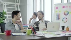 Colegas de trabalho novos do grupo que discutem junto o projeto criativo durante colegas modernos do processo do trabalho no func