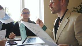 Colegas de trabalho novos que discutem gráficos da renda durante a reunião da equipe Executivos que sentam-se na tabela e na estr video estoque
