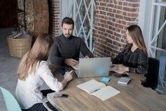 Colegas de trabalho novos que têm o curso de formação usando o laptop moderno para a informação de salvamento imagem de stock royalty free