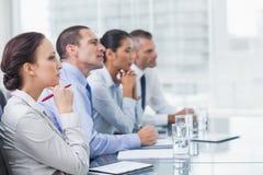 Colegas de trabalho pensativos que escutam a apresentação Fotografia de Stock Royalty Free