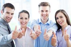 Colegas de trabalho que mostram os polegares acima Fotografia de Stock
