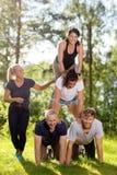 Colegas de trabalho de sorriso que fazem a pirâmide humana no campo gramíneo Foto de Stock