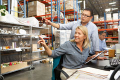 Colegas del asunto que trabajan en el escritorio en Warehouse Fotografía de archivo libre de regalías