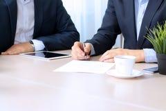Colegas del asunto que trabajan junto El hombre de negocios está firmando un contrato Fotos de archivo libres de regalías