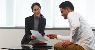 Colegas del negocio que discuten sobre el documento de papel