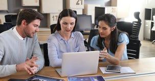 Colegas del negocio que discuten sobre el ordenador portátil 4k almacen de video