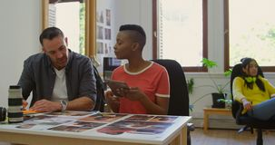 Colegas del negocio que discuten sobre las fotografías en el escritorio 4k almacen de metraje de vídeo
