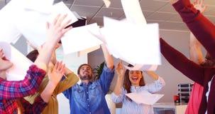 Colegas del negocio que lanzan documentos en el aire