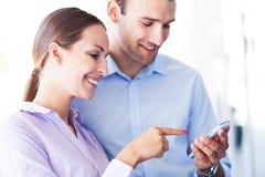 Colegas del negocio que miran el teléfono móvil Imágenes de archivo libres de regalías