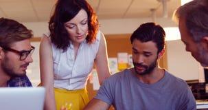 Colegas del negocio que obran recíprocamente con uno a en la reunión