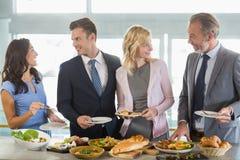 Colegas del negocio que obran recíprocamente mientras que se sirve en el almuerzo de la comida fría fotografía de archivo libre de regalías