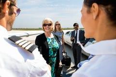 Colegas del negocio que saludan azafata y al piloto Foto de archivo