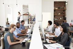Colegas del negocio que trabajan en una oficina abierta ocupada del plan imagen de archivo