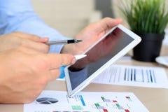 Colegas del negocio que trabajan junto y que analizan figuras financieras en gráficos Fotografía de archivo libre de regalías