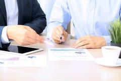 Colegas del negocio que trabajan junto y que analizan figuras financieras en gráficos Foto de archivo