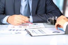 Colegas del negocio que trabajan junto y que analizan figuras financieras en gráficos Imagen de archivo libre de regalías