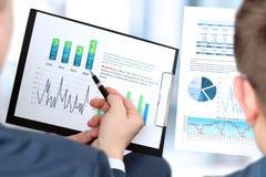 Colegas del negocio que trabajan junto y que analizan figuras financieras en gráficos Imágenes de archivo libres de regalías
