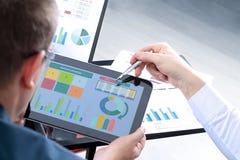 Colegas del negocio que trabajan y que analizan figuras financieras en una tableta digital Foto de archivo libre de regalías