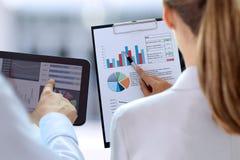 Colegas del negocio que trabajan y que analizan figuras financieras en gráficos Imágenes de archivo libres de regalías