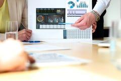 Colegas del negocio que trabajan y que analizan figuras financieras en gráficos Fotos de archivo libres de regalías