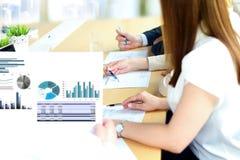 Colegas del negocio que trabajan y que analizan figuras financieras en gráficos Fotografía de archivo libre de regalías