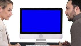 Colegas del negocio un hombre y una mujer que tienen una charla sobre cuál está en la pantalla del ordenador, fondo blanco azul almacen de metraje de vídeo