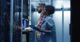 Colegas diversos da TI que ajustam o hardware do servidor imagem de stock