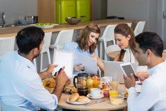 Colegas do negócio que discutem sobre a tabuleta digital ao comer o café da manhã Fotografia de Stock